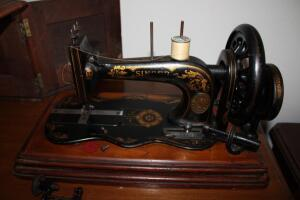 Antique hand crank Singer sewing machine in wooden box with key